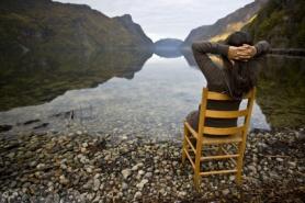 woman in chair near lake shores