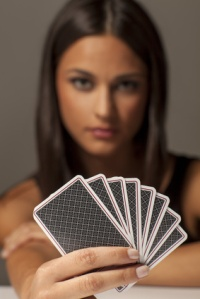 beautiful attractive girl holding poker cards
